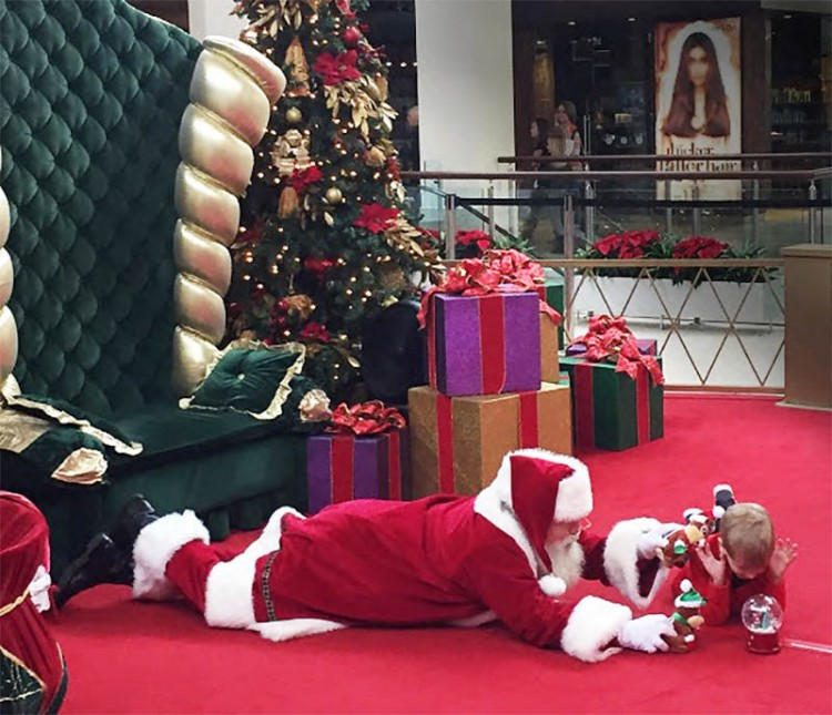 santa lays on the floor to play with boy with autism