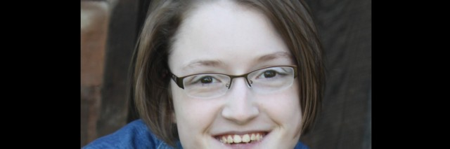 A smiling young woman with glasses