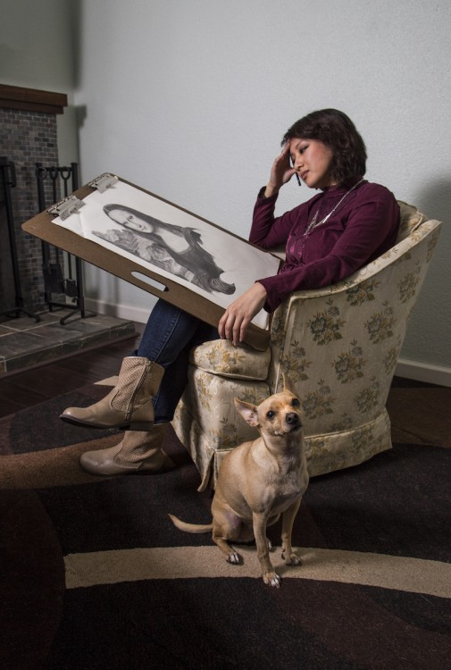 Woman holding a sketch with a dog by her side