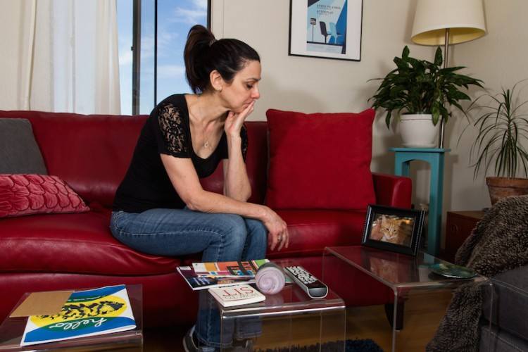 A woman sits on her couch and stares at a picture of her cat