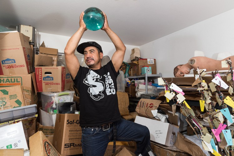 A man holds a sphere in a storage room