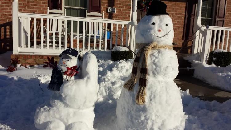 Two snowmen, one in a wheelchair.