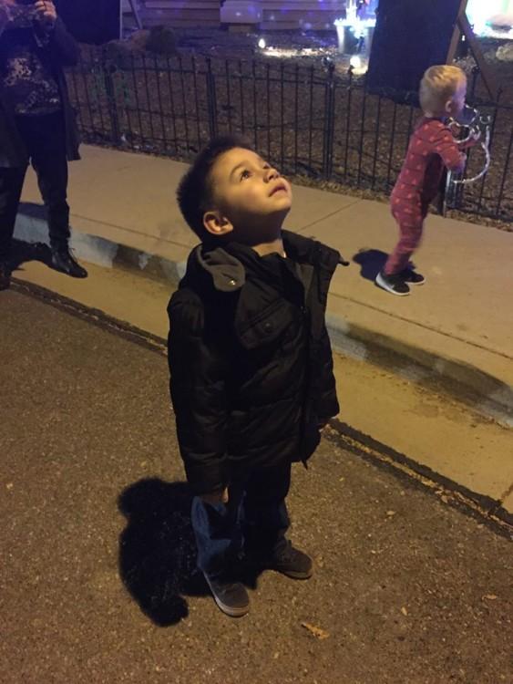 boy wearing black jacket looking up