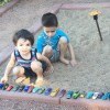 Two brothers playing in sandbox with toy cars