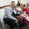 Dad and mom smile next to daughter in wheelchair