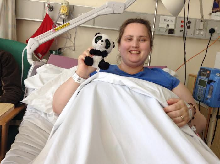 Angela in the hospital holding a stuffed panda