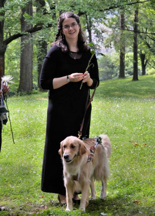 woman standing on grass next to dog