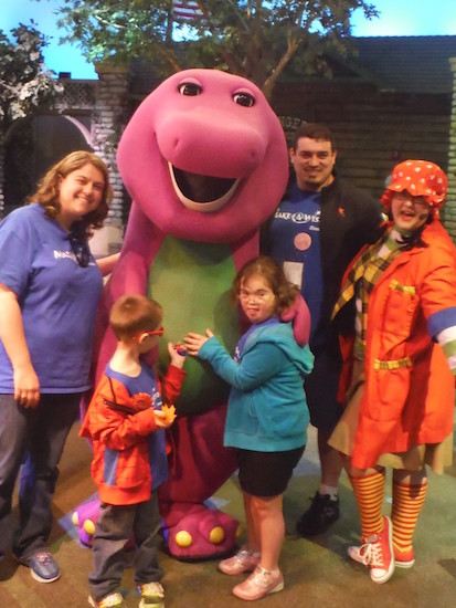 family posting for a photo with Barney the Dinosaur