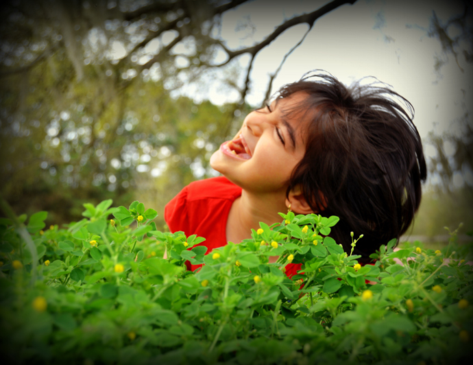 Girl smiling outdoors in front of a plant