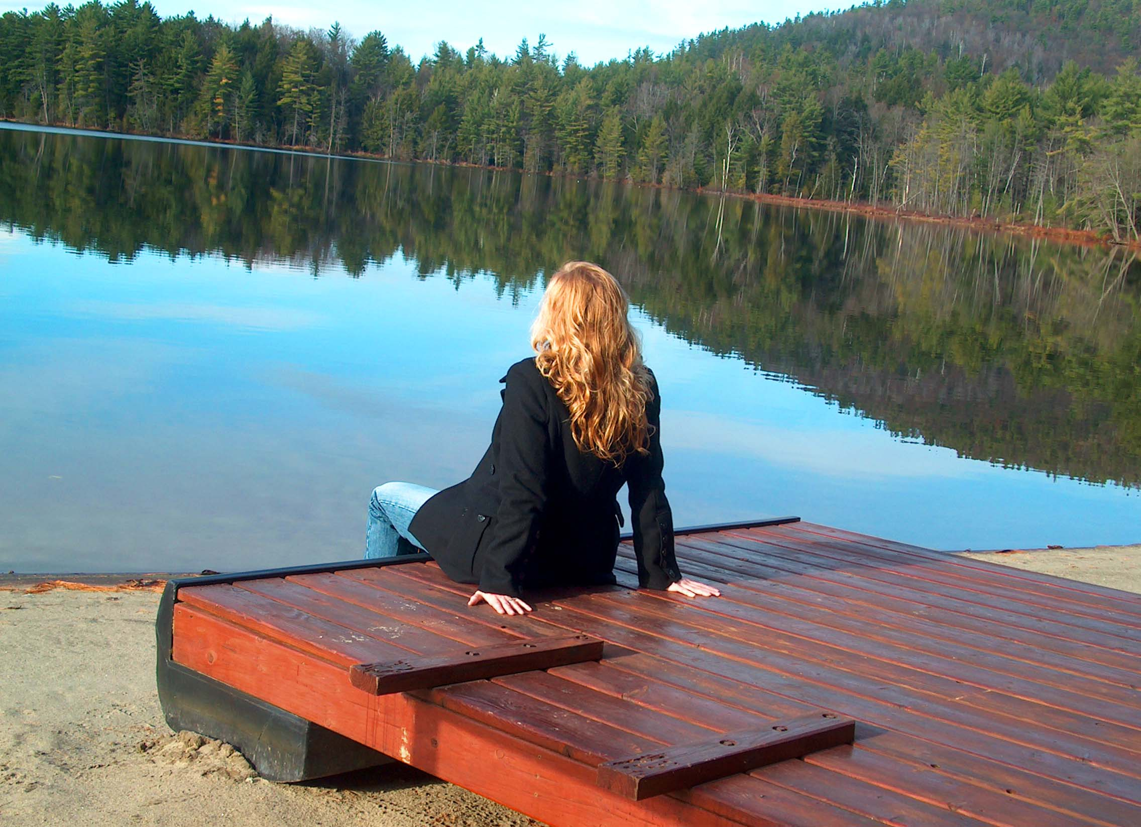 A photo of Kathy taken on her honeymoon in Lake George, New York. She is sitting next to the water and looking at the landscape.