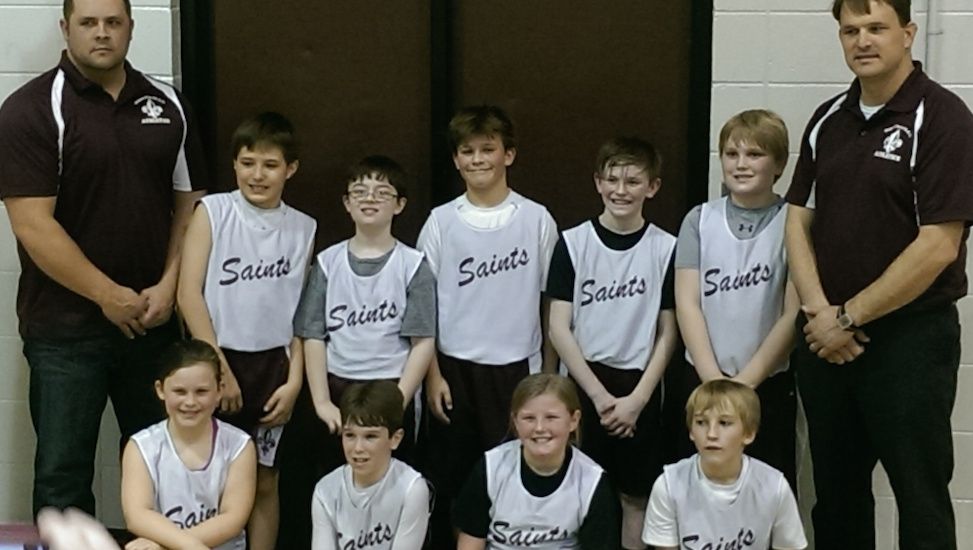 Kids' basketball team and coaches posing for a photo