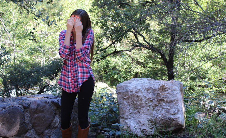 Claudia standing in a park with her hands covering her face