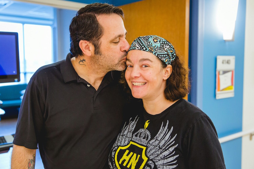 woman smiling and looking at the camera, man with eyes closed kissing her forehead