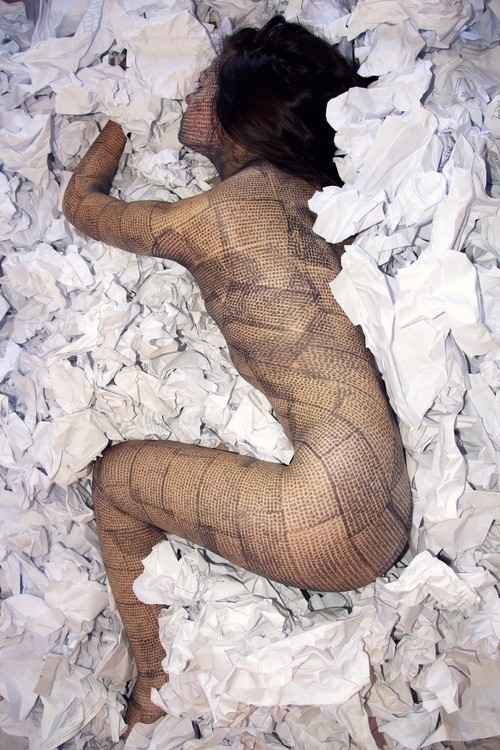 Stone lays curved up in a pile of crinkled tissue paper. Her body is printed with lines.