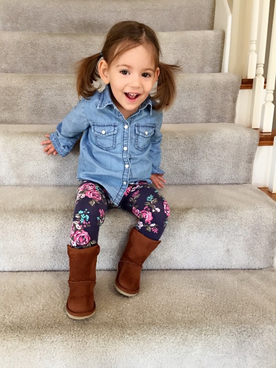 Little girl with pig-tails smiles on staircase in home