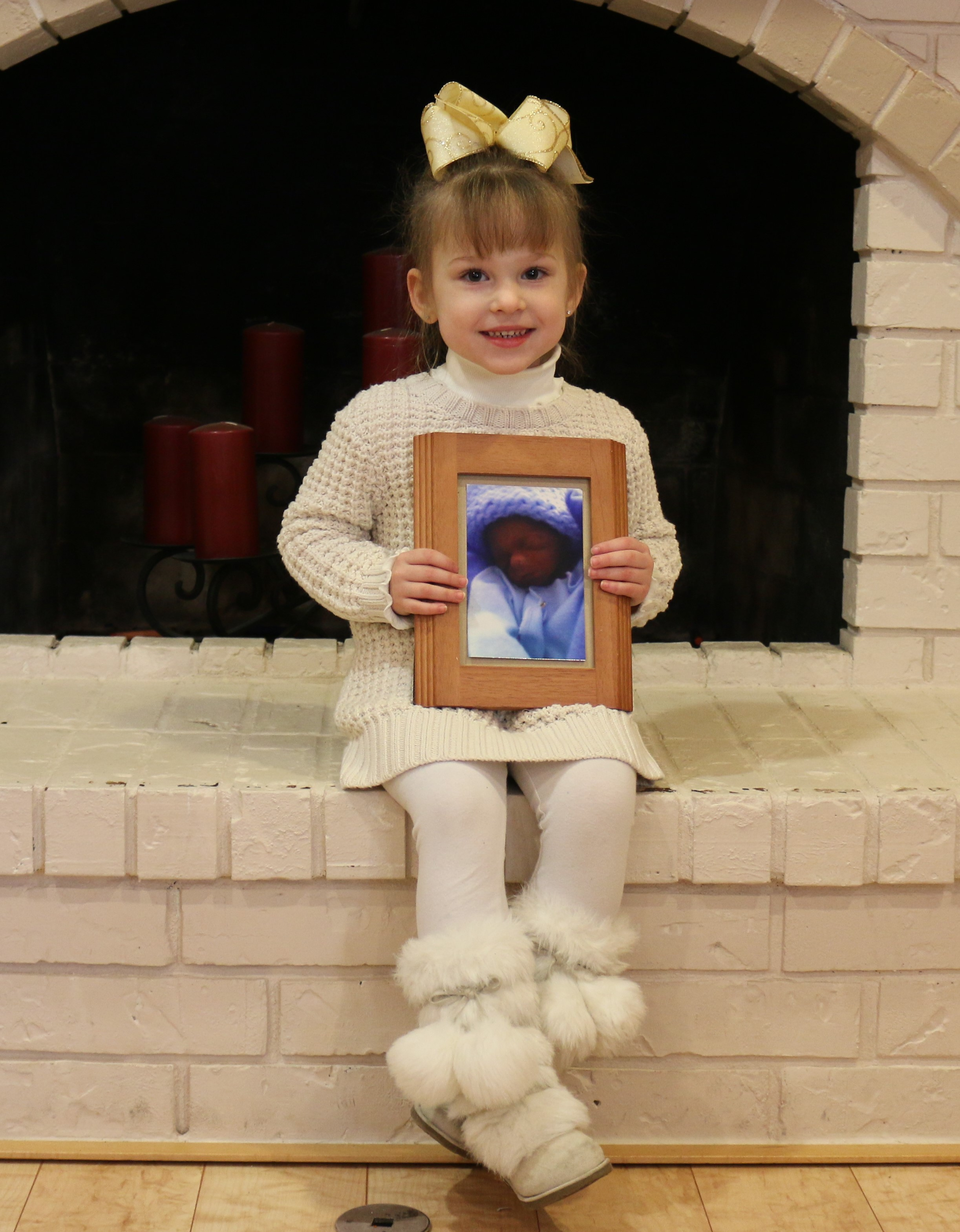 Amanda's daughter holding a picture of her brother