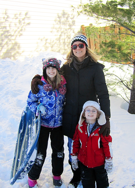 mom and her children outside in the snow