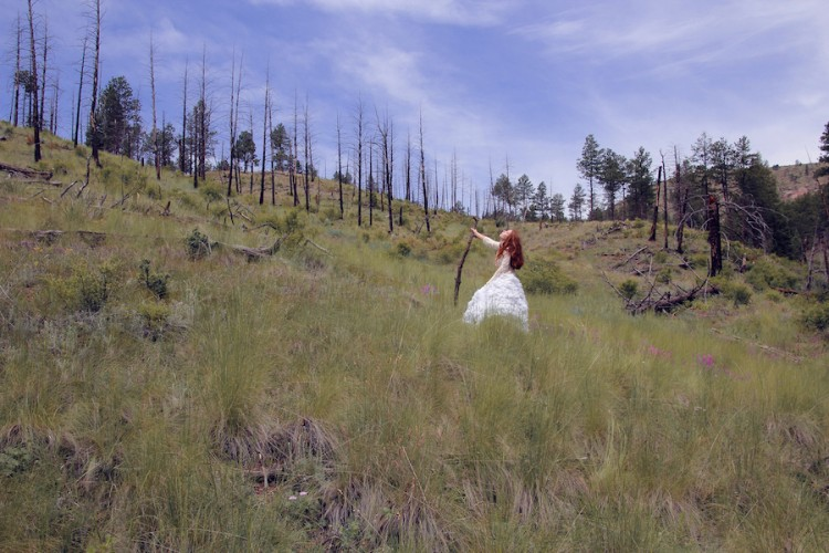A woman with red hair stands in a bare field. She holds a walking stick and looks upwards.