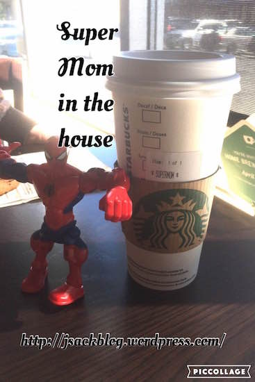 """Starbucks cup next to a Spider-Man action figure with the words """"Super Mom in the house"""" across the photo"""