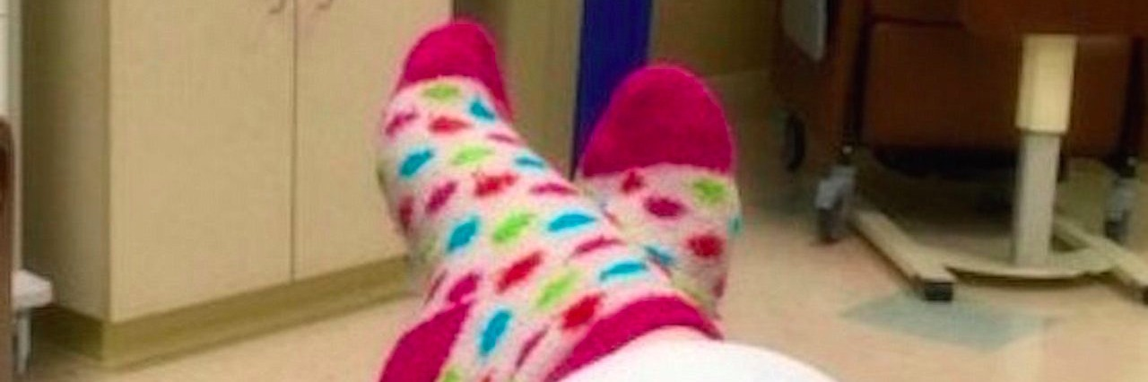woman takes photo of her feet while lying in bed for a medical test