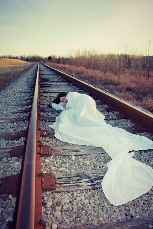 Stone lays on train tracks in a white gown.
