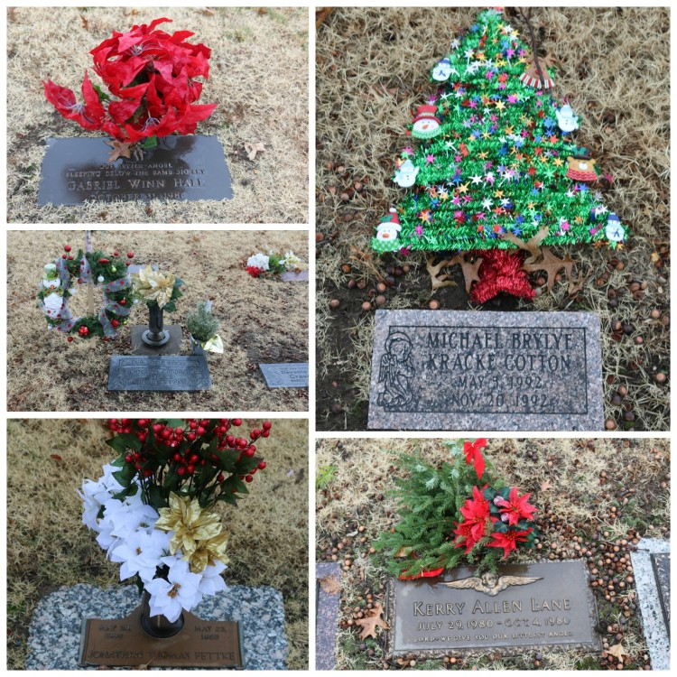 Several different headstones with Christmas flowers and decorations on them.