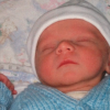 newborn baby wearing hat and sweater