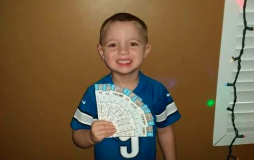 little boy holding detroit lions tickets