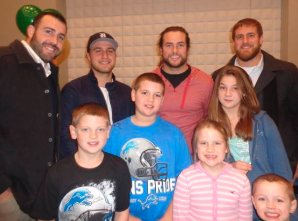 kids standing with detroit lions football players