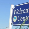 a blue and white welcome center sign