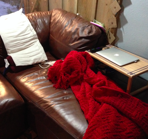 couch, red blanket and table with laptop