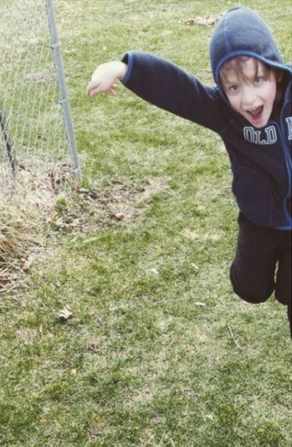 Jennifer's son is wearing a blue hoodie standing outside by a fence. The photo captures him mid-jump.