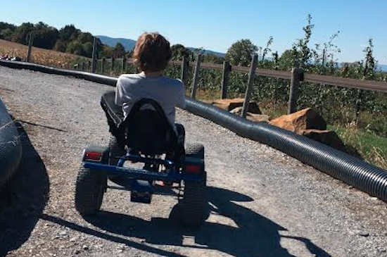 boy riding on wheeled vehicle on track