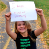 Jade's daughter is smiling and holding a sign that says, I have bipolar disorder! She is wearing a shirt that says World Mental Health Day.