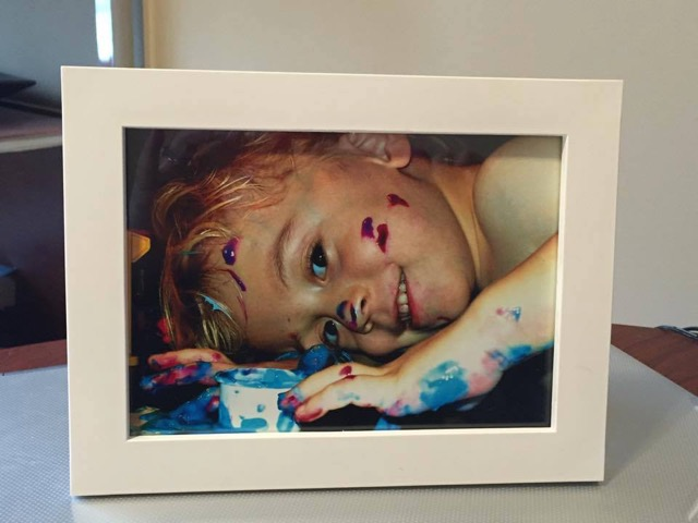 A framed photo of Katie's son with paint on his face and hands