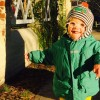 little boy in green jacket outdoors