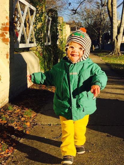little boy wearing green jacket outdoors