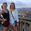 two women standing next to railing overlooking florence, italy