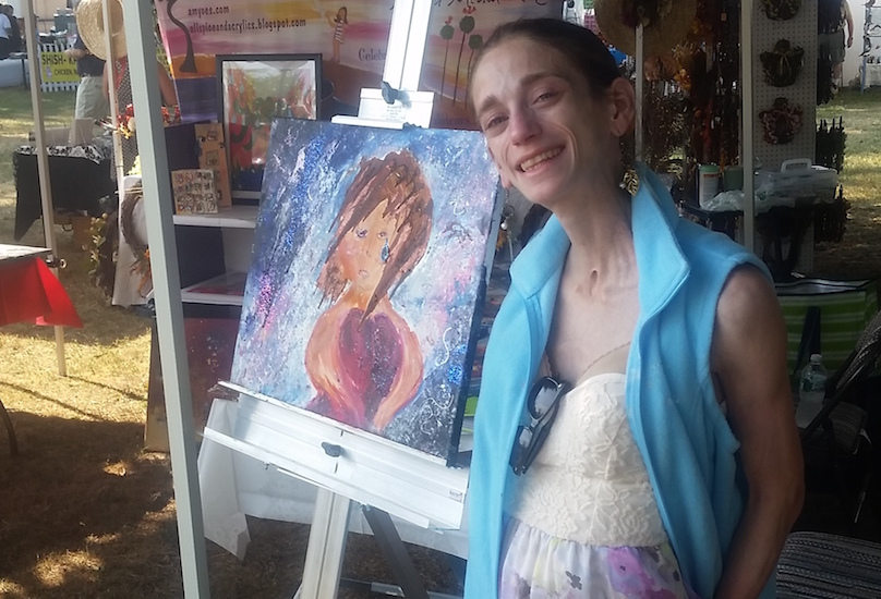 Amy standing next to her artwork at an outdoor art festival