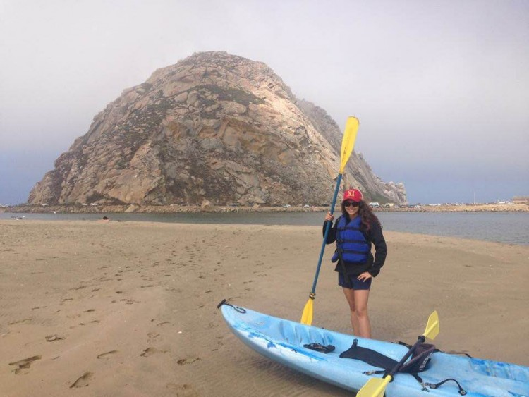 woman standing with kayak in front of rock