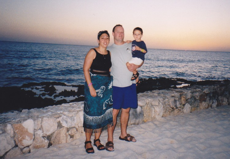 mom, dad and toddler in front of ocean