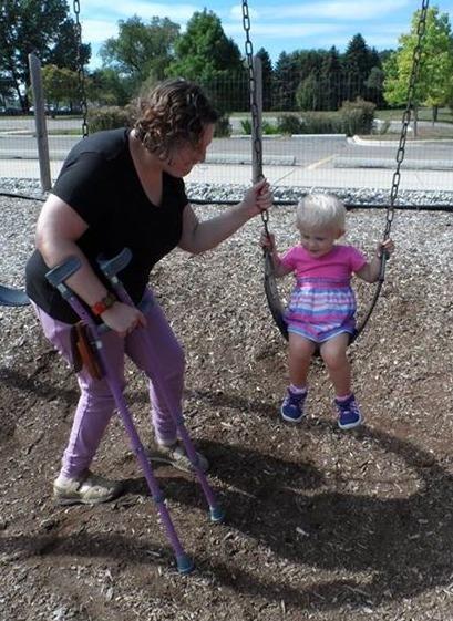 mom pushing young girl on swings