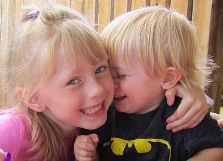 Kathy's children have light blonde hair. Her daughter has her arm around her son.