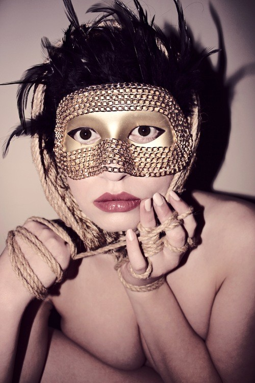 Stone stares into the camera, wearing a golden mask. Her hands are tied together with rope.