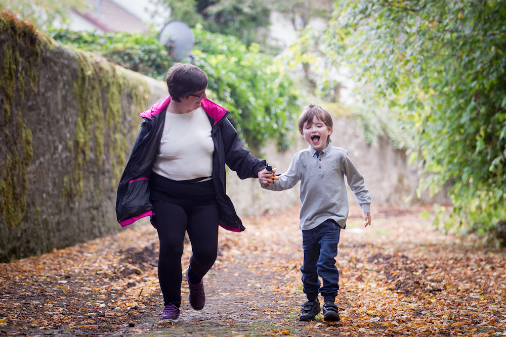 mom and son holding hands running outside