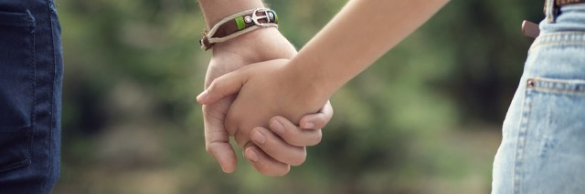 Young couple holding hands, focus on hands