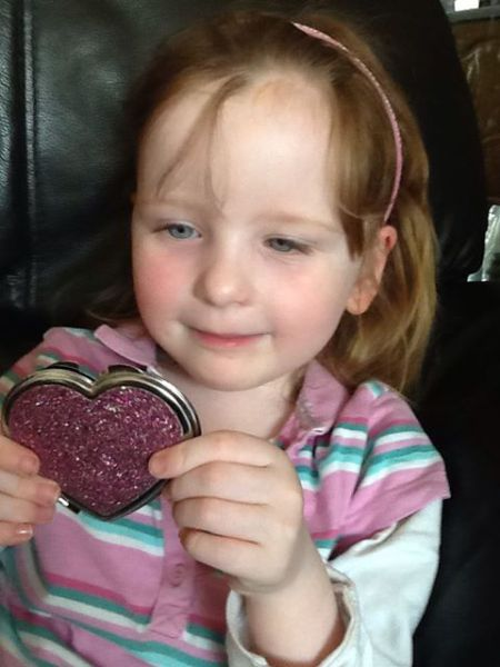 Little girl holding heart-shaped pink mirror