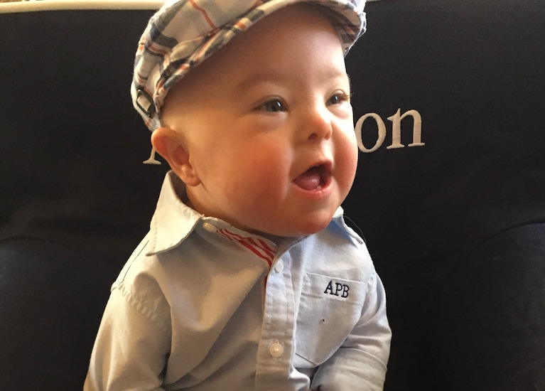 Toddler wearing a cap and button-down shirt