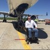 a man in a wheelchair in front of an airplane on a landing strip