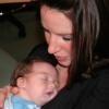 mom with dark hair holding newborn baby